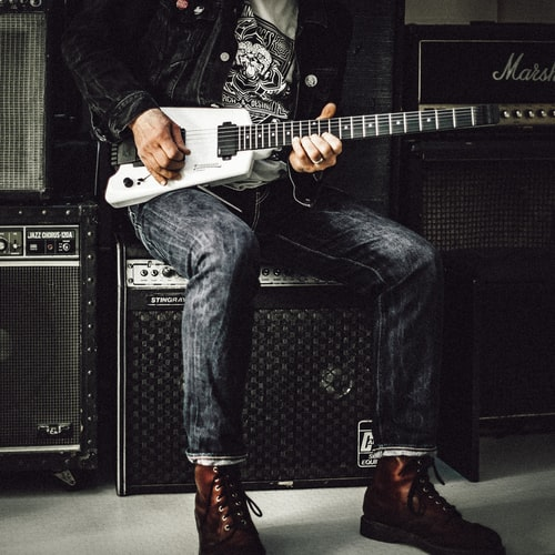 man wearing a black jacket, white shirt, blue jeans, and brown boots, playing a white electric guitar while sitting on an amp
